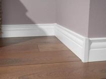 Белый широкий плинтус в оформлении комнаты