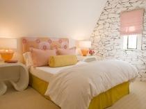 Декорирование стены на мансардной спальне камнем
